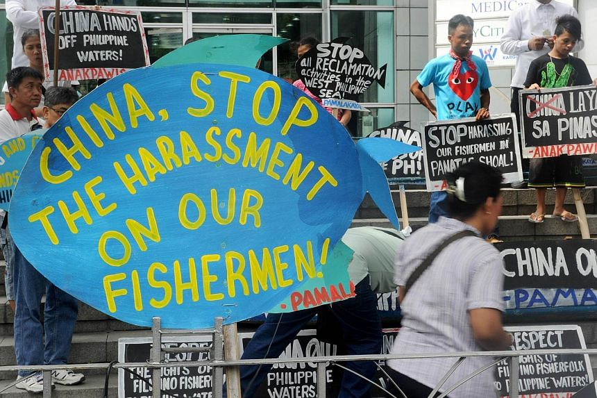 Activists hold a rally in front of the Chinese consulate in Manila's financial district on July 3, 2015 to protest China's reclamation works in the South China Sea.