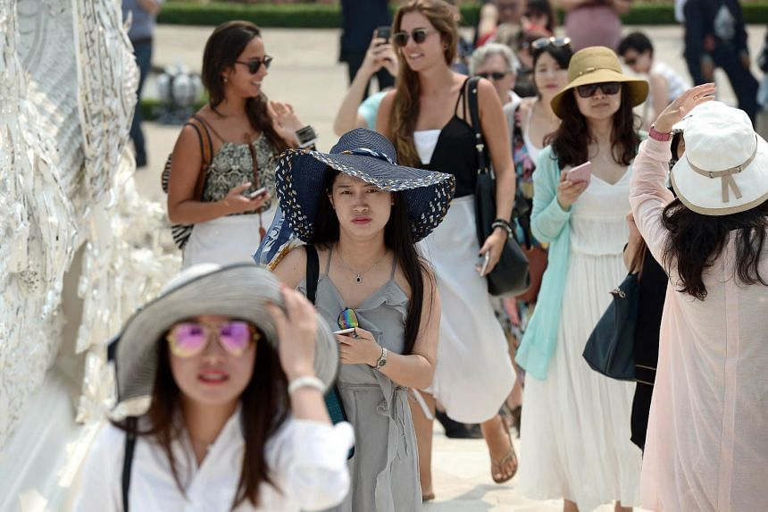 Chinese tourists visiting the White Temple in Chiang Rai, northern Thailand, on April 7, 2015.