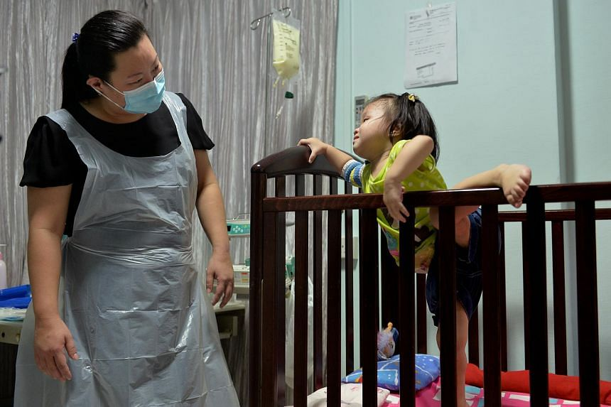 Madam Yeo keeping a watchful eye as an active Hwee Suan tries to climb out of her cot.