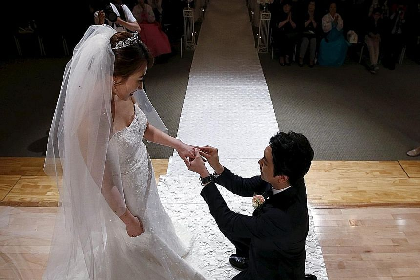 I do... want a modest wedding ceremony. Here, a couple tie the knot at a budget wedding, held at the National Library of Korea in Seoul. To boost marriage rates, the government is renting out public buildings cheaply.