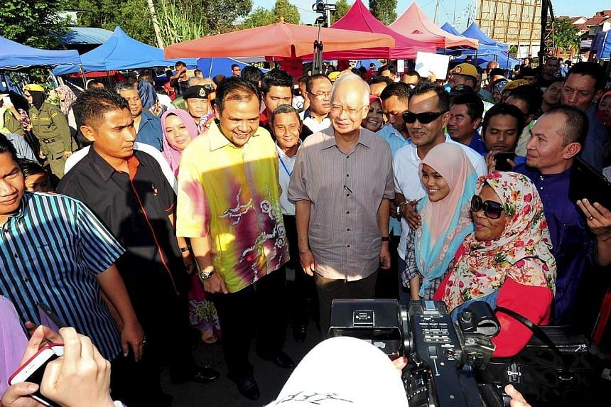 Malaysian PM Najib Razak (centre) at a Ramadan bazaar in Semenyih in Selangor yesterday. The Wall Street Journal reported on Friday that he had received up to $940 million in personal accounts in AmBank between March 2013 and February this year. Mala