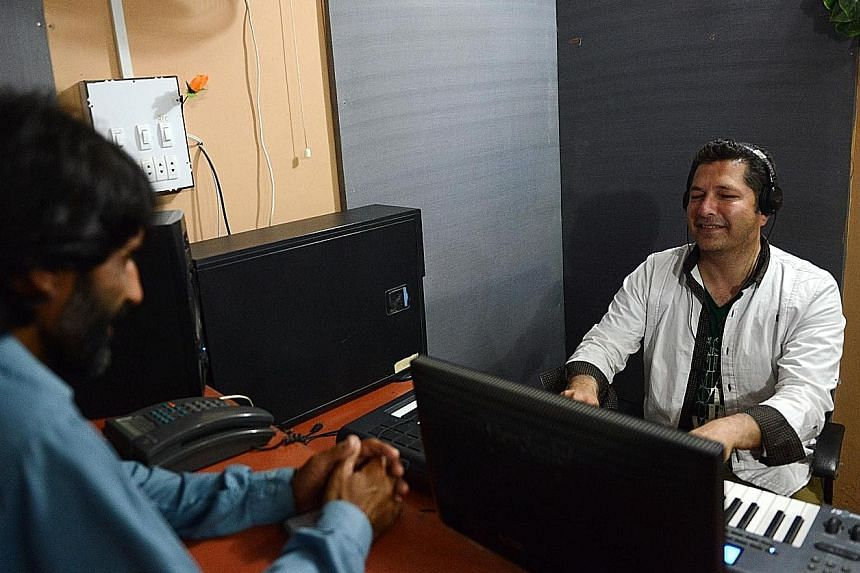 Pashto singer Bakhtiar Khattak (right) recording a song. The violence of Pakistan's bloody insurgency has been injected into catchy pop lyrics after over a decade of war against the Taleban.