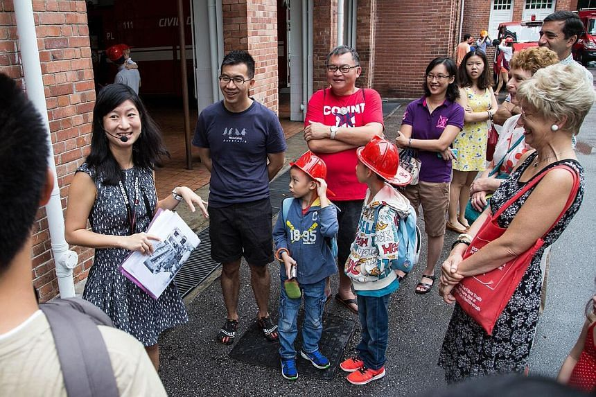 Volunteer guide Lee Ai Ling offered a glimpse of the lives lived behind some of Singapore's old monuments. Among the 18 who joined her tour were Mr David Siauw (in blue) with two of his children.