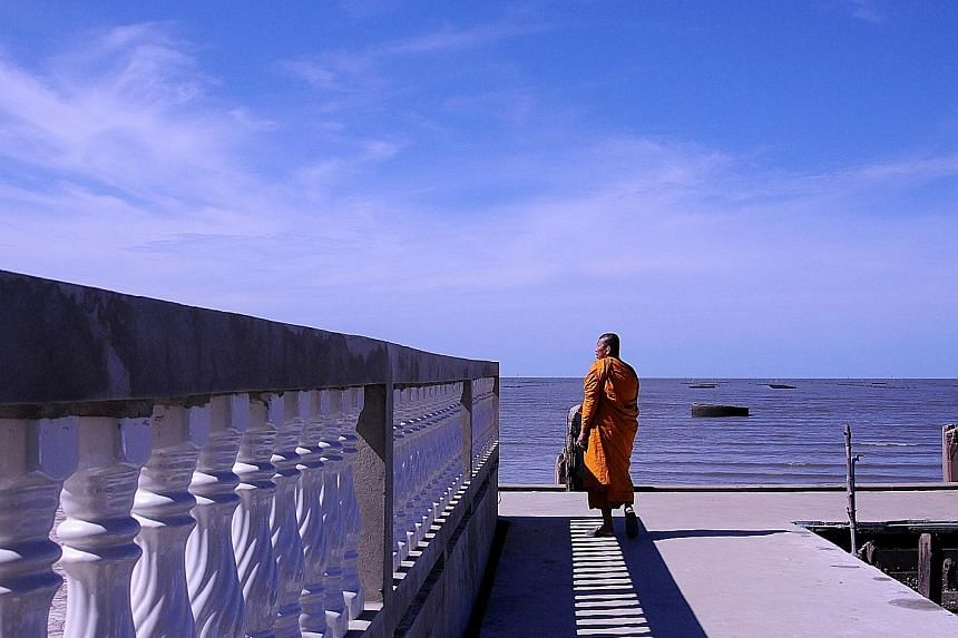 Phra Somnuek Athipanyo, the abbot of Wat Khun Samut, a Buddhist temple on the coast of the Gulf of Thailand some 30km south of Bangkok, patrols the parapet inspecting his temple's defences against the sea.