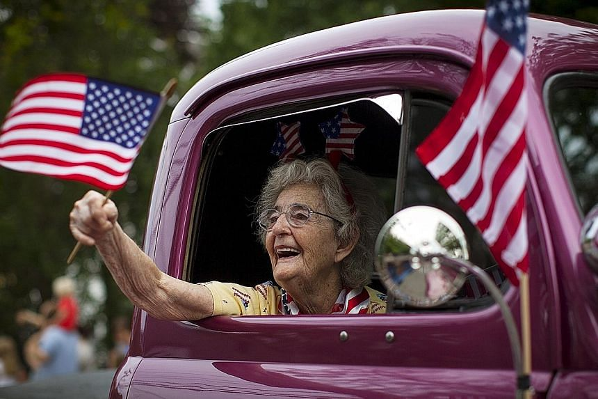 A flag-waving woman is all smiles at an Independence Day parade in Barnstable, Massachusetts