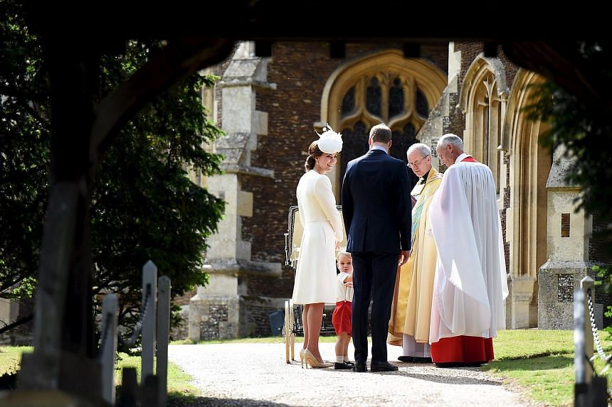 Prince George turns to look at the crowds as Princess Charlotte, Prince William (in black) and Catherine (in white), Duchess of Cambridge are greeted by Reverend Canon Jonathan Riviere (right) and the Archbishop of Canterbury, Justin Welby (second fr