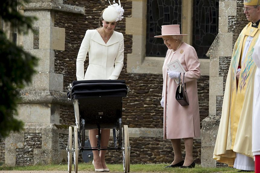 Britain's Queen Elizabeth (right) is seen standing with Catherine, Duchess of Cambridge, and Princess Charlotte after her christening at the Church of St. Mary Magdalene.
