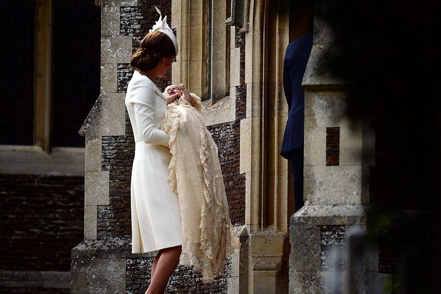 Catherine, Duchess of Cambridge, carries her daughter, Princess Charlotte of Cambridge after taking her out of a pram as they arrive for Charlotte's Christening at St. Mary Magdalene Church.
