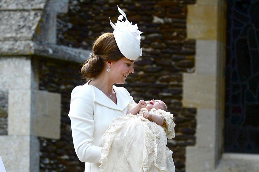 Catherine, Duchess of Cambridge, carries her daughter, Princess Charlotte of Cambridge after taking her out of a pram.