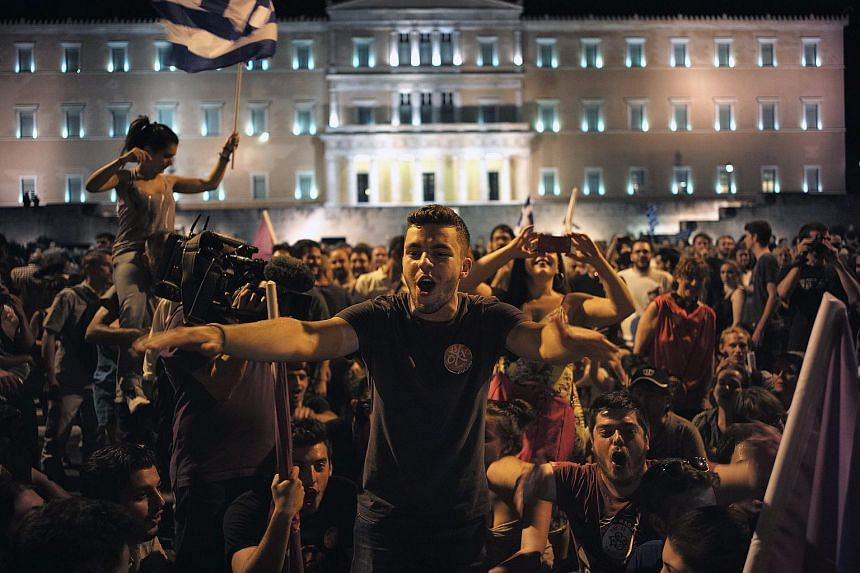 Supporters of the ruling Syriza party celebrate their victory in a referendum by the parliament in Athens, Greece on July 5, 2015.
