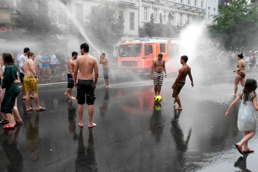 People shower in the street to cool down as fire brigades use their equipment to refresh residents and visitors during a hot summer day on July 5, 2015 in Berlin's Prenzlauer Berg district.