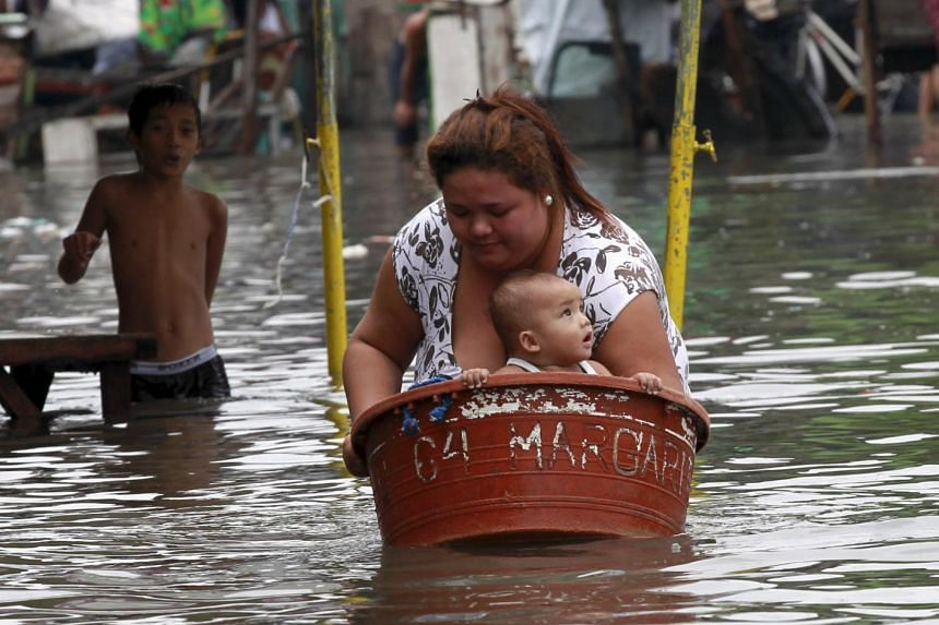A mother puts her baby in a basin while she wades in waist-deep flooding caused by typhoon Linfa, locally named Egay, at Longos town in Malabon city, north of Manila, on July 6, 2015.