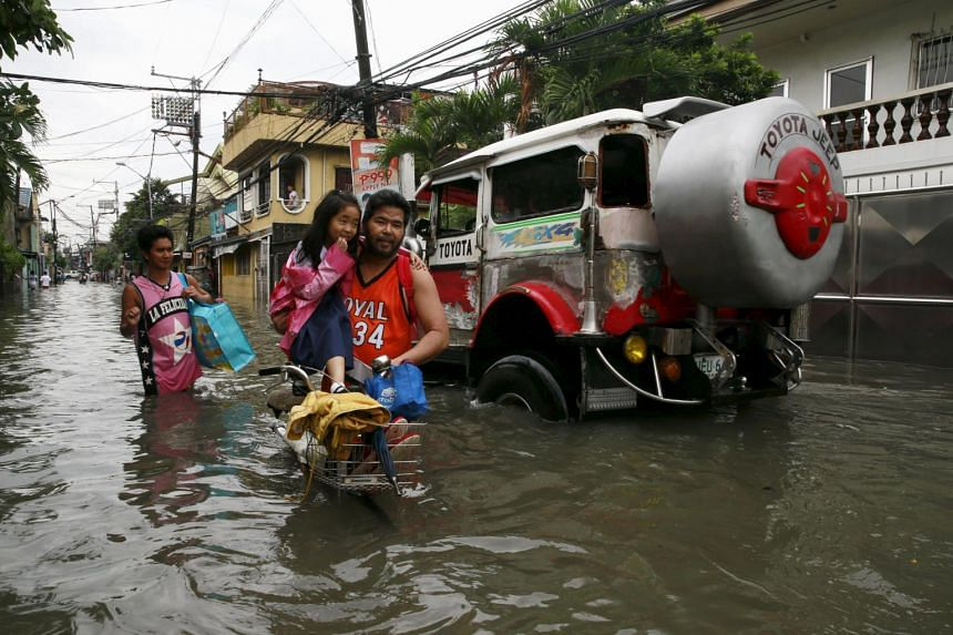 A father holds his daughter as they wade through waist-deep flooding caused by typhoon Linfa, locally named Egay, at Longos town in Malabon city, north of Manila, on July 6, 2015.
