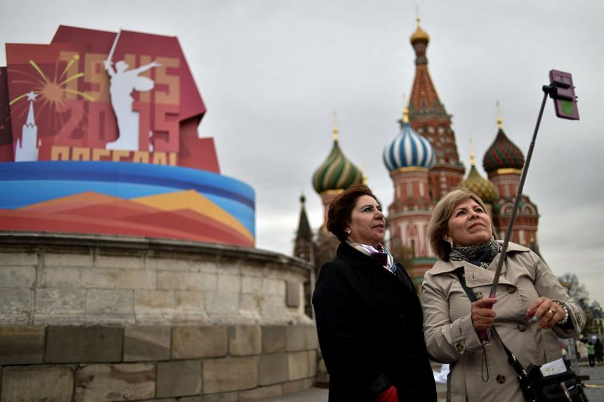 Women pose for a selfie in front of the historical Place of Execution in Moscow, on April 30, 2015.