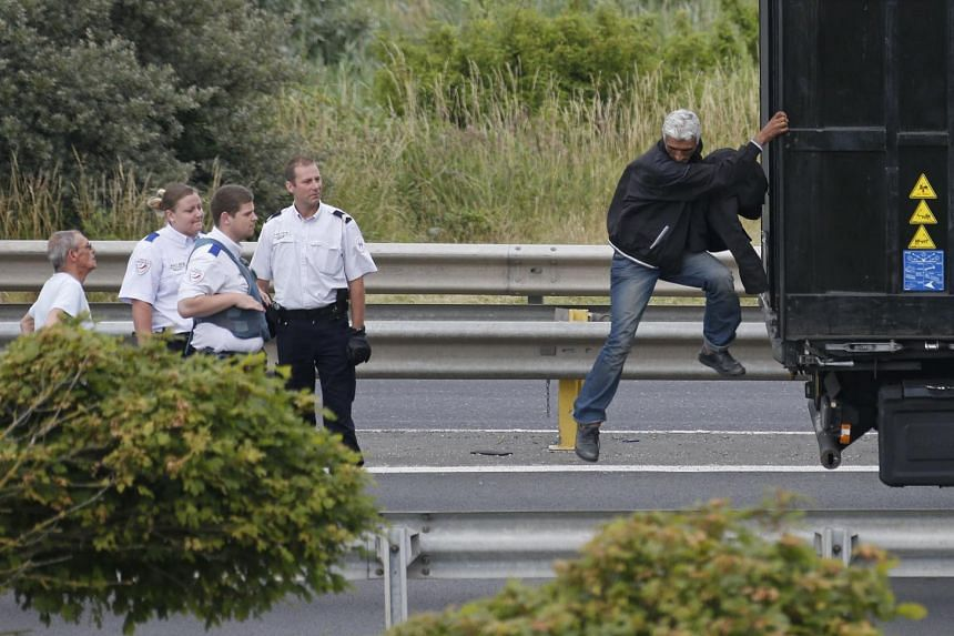 French police tell a migrant to get off a truck after he attempted to make a clandestine crossing to England through the Channel Tunnel, in Coquelles near Calais, northern France, on July 2, 2015.