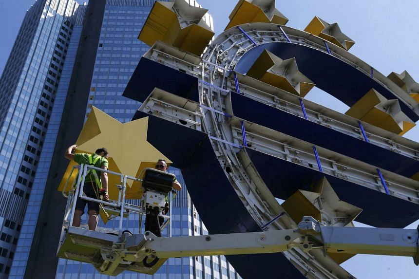 Workers dismantle the large Euro sign sculpture for maintenance, in front of the headquarters of the former European Central Bank (ECB) in Frankfurt, on July 6, 2015.