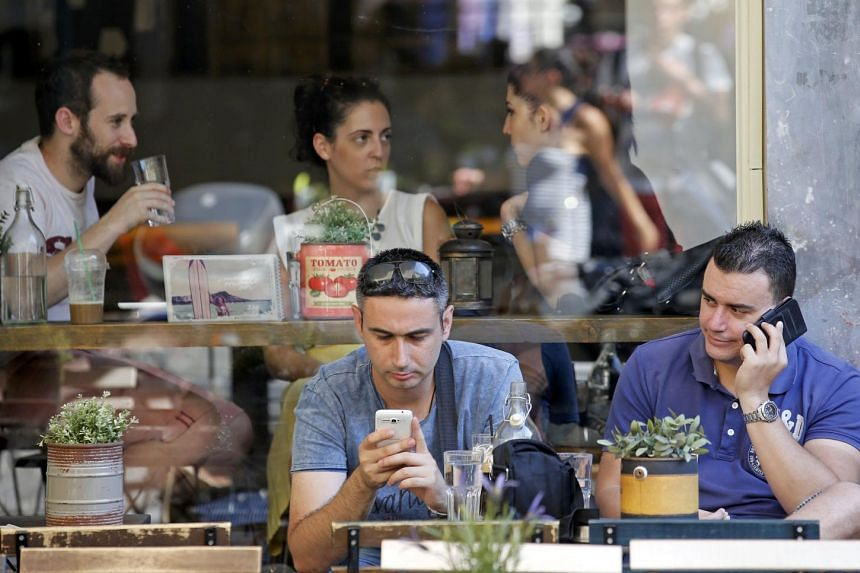 People drink on a terrace in central Athens, Greece on July 6, 2015.
