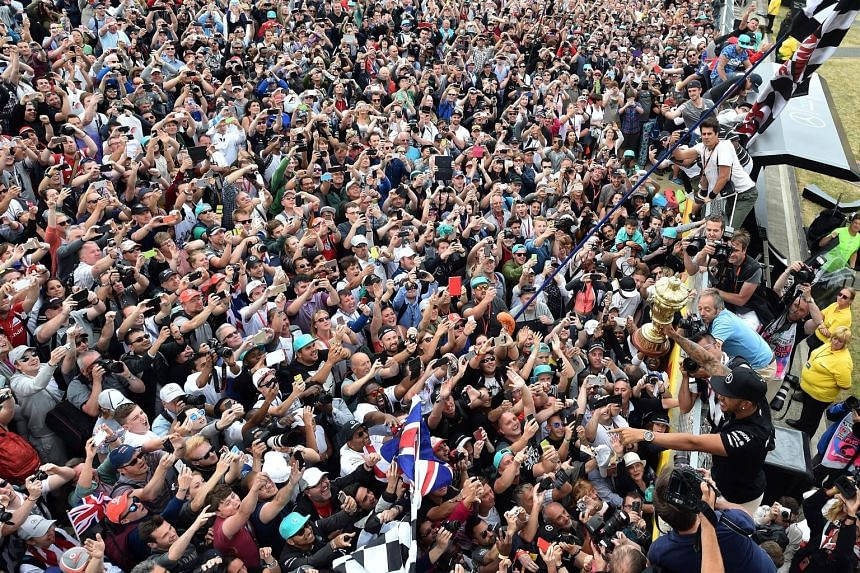 Mercedes driver Lewis Hamilton showing off his trophy to adoring home fans as he celebrates after winning the British Grand Prix for the third time at Silverstone.