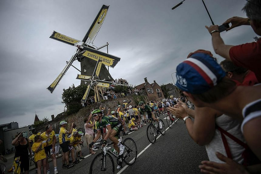 France's Thomas Voeckler rides past a windmill as supporters cheer during the 166km second stage of the Tour de France. BMC team's Tejay van Garderen is ahead of the favourites for now.