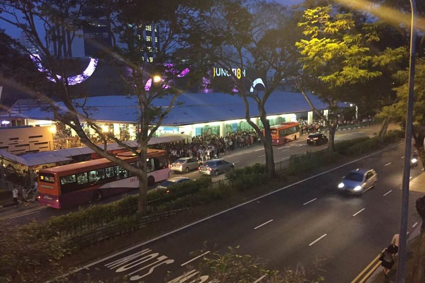 Commuters queue for buses outside Bishan MRT Station on July 7, 2015.