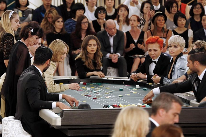 French actress and singer Vanessa Paradis (third left) and British singer Rita Ora (second right) at a casino table with other guests.