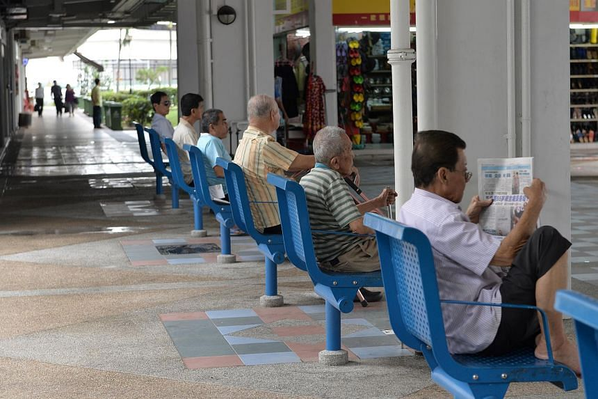 Elderly men sit in a row at the foot of a block in Chin Swee estate.