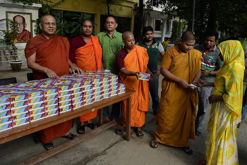 Bangladeshi Buddhist monks giving out Iftar meals, food for breaking the daytime fast, to Bangladeshi Muslims at the main shrine of Dhammarajika Monastery in Dhaka on July 6, 2015.