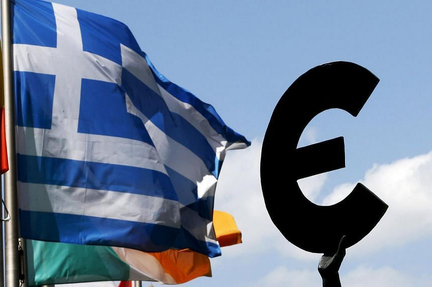 A Greek flag flying past a statue depicting European unity outside the European Parliament.