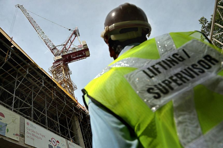 A lifting supervisor watching as a crane operator does safety checks at a construction site.