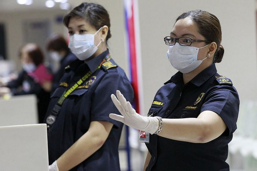 A customs inspector wearing a face mask as she waits for passengers arriving from South Korea at the Ninoy Aquino International Airport in Manila.