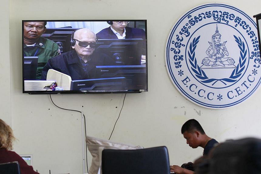 Journalists work next to a TV screen broadcasting the live feed of former Khmer Rouge leader Nuon Chea's trial, in Phnom Penh, Cambodia, on July 2, 2015. US judge Mark Harmon resigned from the UN-backed war crimes trials in Cambodia on Tuesday, July