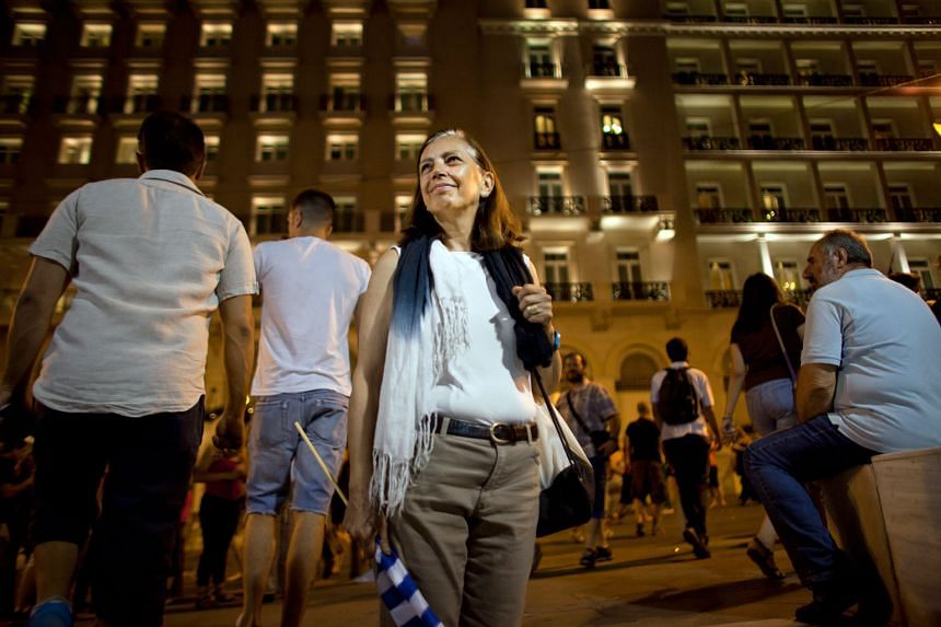 Ms Anthi Panagiotidou is pleased with the outcome of the bailout deal referendum. She joined others at Syntagma Square in Athens yesterday to celebrate.