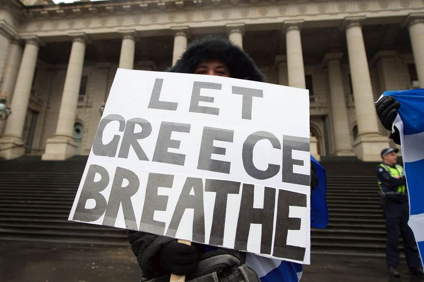 A fishmonger in despair in Athens while halfway across the world, in Melbourne, Australia (above), protesters rallied in solidarity with Greece.