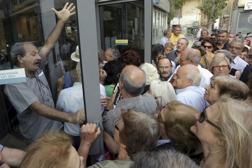 Pensioners in Crete struggling to enter a Greek National Bank branch to receive part of their pension.
