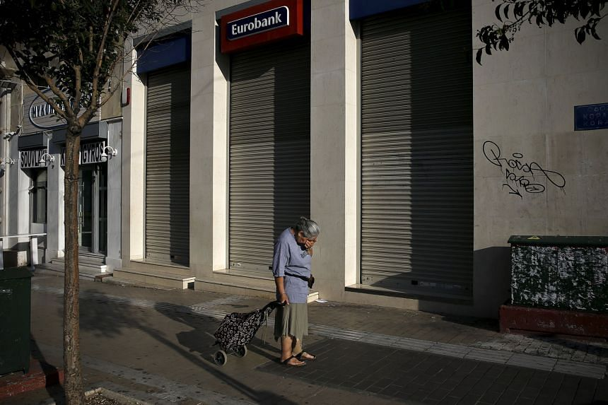 A dejected woman pulling a shopping cart outside a closed Eurobank branch in Athens.