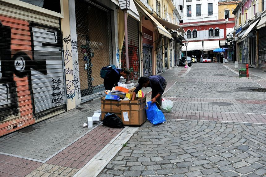 Men searching cardboard garbage boxes next to closed businesses in Thessaloniki.