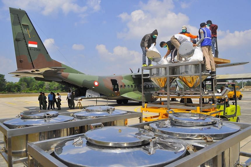 Indonesian officials loading chemicals for cloud seeding onto an air force plane in Pekanbaru, Riau province, on Friday.
