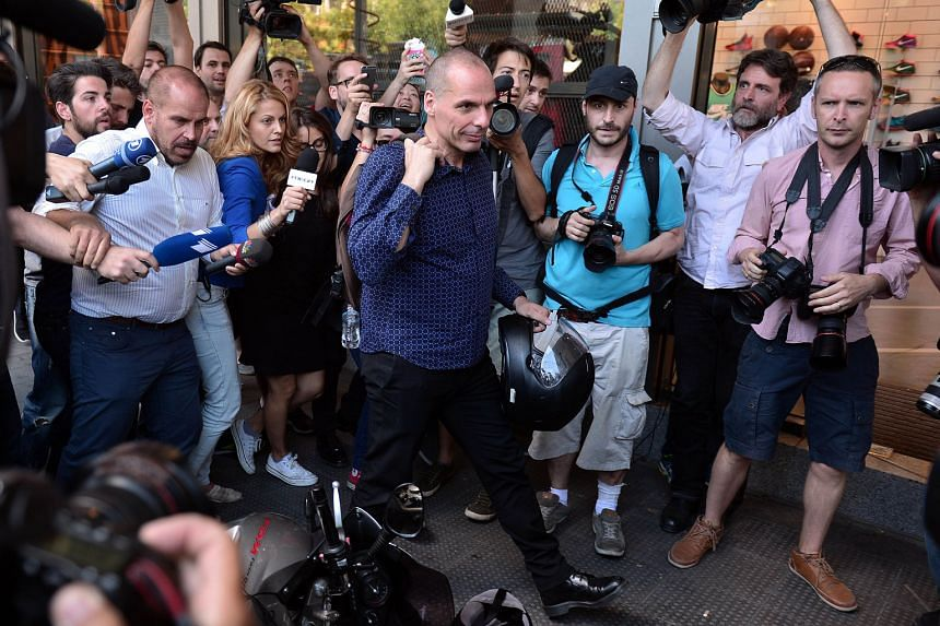 Outgoing Greek Finance Minister Yanis Varoufakis (centre) leaving the ministry in Athens yesterday. He said Prime Minister Alexis Tsipras believed his resignation  would help smooth the path to a new aid deal.