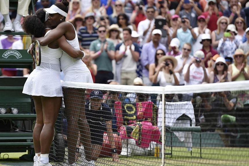 Serena Williams (left) embraces Venus Williams after winning their match at the Wimbledon Tennis Championships in London, on July 6, 2015.