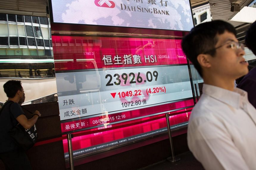 Pedestrians walk past an electronic display showing the Hang Seng Index figure in Hong Kong, China, on July 8, 2015.