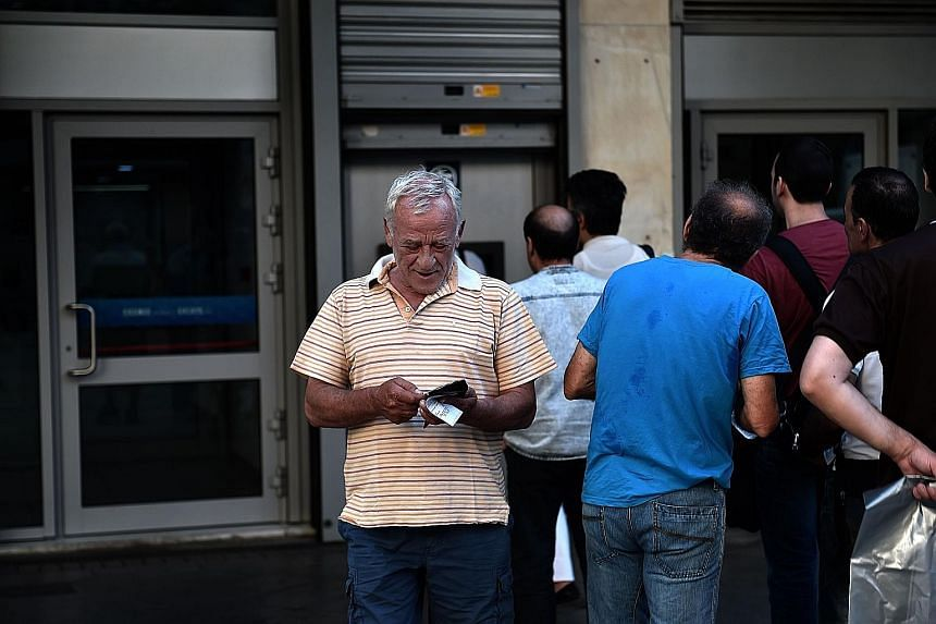 A queue at an ATM in Athens yesterday. Banks will stay shut for two more days, after the European Central Bank denied a request for more emergency funding.