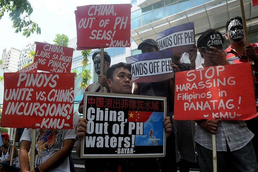 Protesters brandishing placards at a rally in front of the Chinese Consulate in Manila's financial district yesterday, denouncing China's claims on most of the South China Sea. China is not taking part in the Permanent Court of Arbitration hearing, b