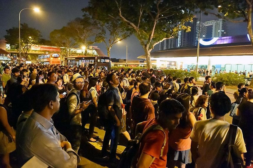 Commuters outside Bishan MRT station (far left) waiting for buses after train services were disrupted last night. Over at City Hall MRT station, commuters snapped photos of a signboard displaying information on the disruption of services on the East-