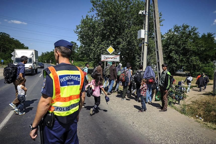 Police officers helping a group of illegal migrants to cross a road near the refugee camp in Debrecen, 221km from Budapest, last week.
