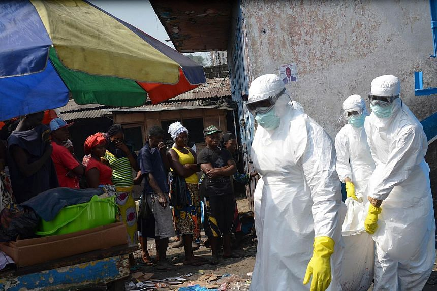 A Jan 5 photo shows red cross workers carrying the body of a person who died from Ebola, in Monrovia.
