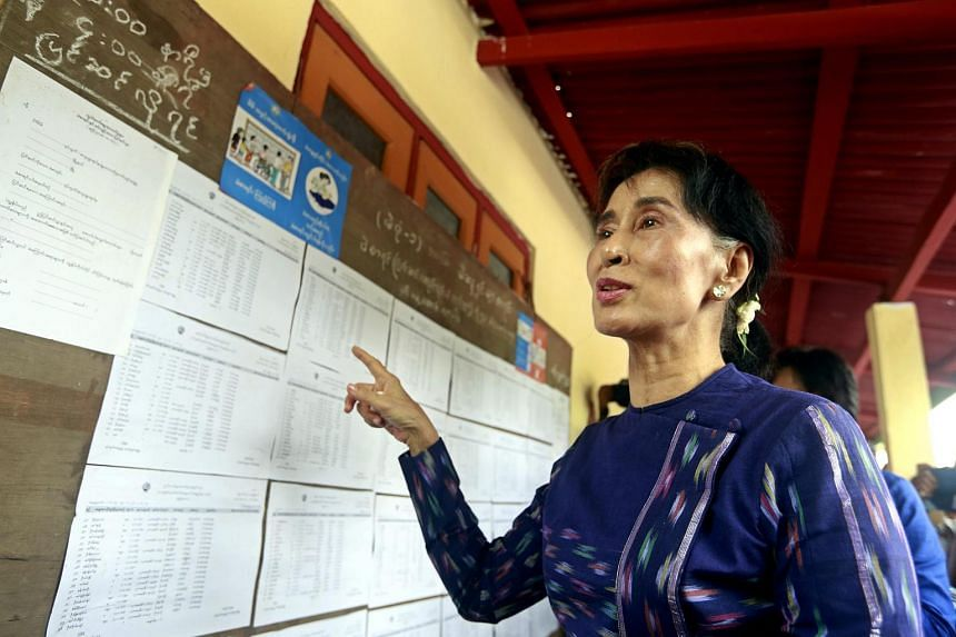 Myanmar opposition leader Aung San Suu Kyi (centre) talks to media as she checks the voters list at the Wahtheinkha village in Kawmhu township, Yangon, Myanmar on July 4, 2015.