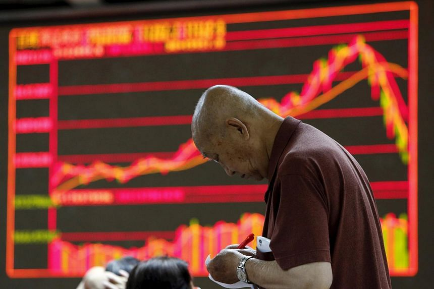 An investor takes notes in front of an electronic board showing stock information at a brokerage office in Beijing, China.