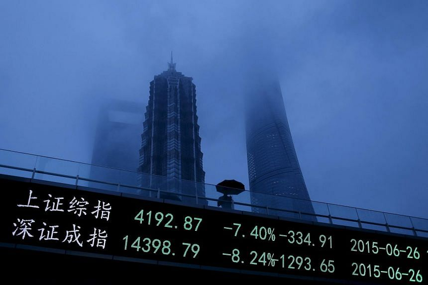 A man walks past an electronic board showing the benchmark Shanghai and Shenzhen stock indices.
