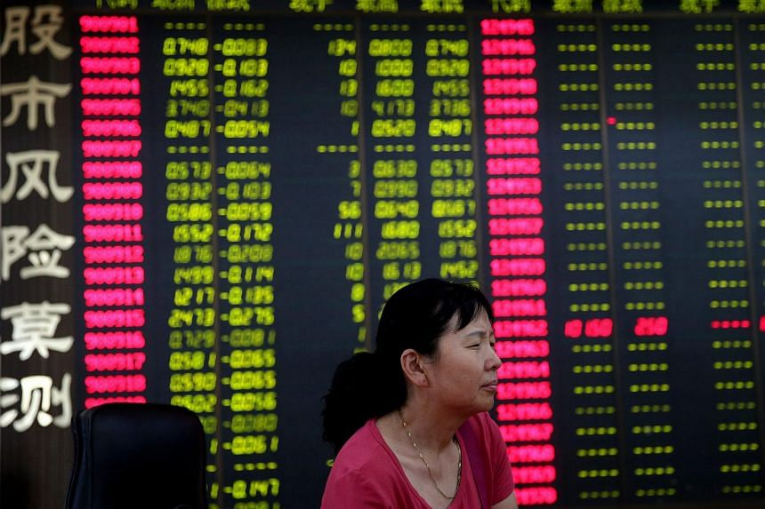 A stock investor rests in front of an electronic screen showing stock prices.