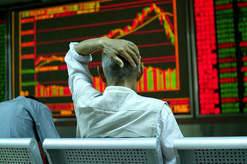A stock investor sits in front of an electronic screen showing stock price at a brokerage house in Beijing city, China, July 6, 2015.